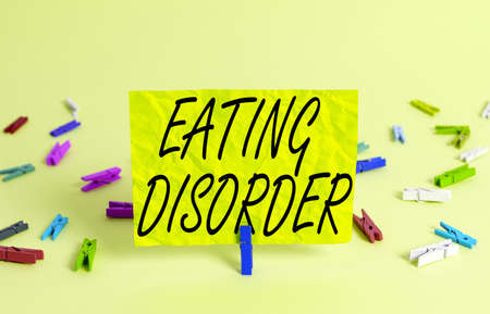 Text sign showing Eating Disorder. Business photo text illnesses or severe disturbances in their eating behaviors Colored crumpled rectangle shaped reminder paper light blue background