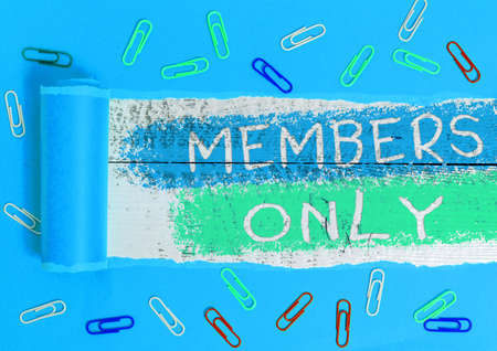 Text sign showing Members Only. Business photo showcasing Limited to an individual belongs to a group or an organization Rolled ripped torn cardboard placed above a wooden classic table backdrop