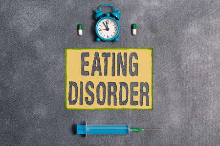 Word writing text Eating Disorder. Business photo showcasing illnesses or severe disturbances in their eating behaviors Set of medical equipment with notepad for health condition assessment
