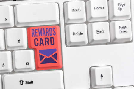 Handwriting text Rewards Card. Conceptual photo Help earn cash points miles from everyday purchase Incentives Different colored keyboard key with accessories arranged on empty copy space Stock Photo