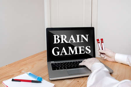 Writing note showing Brain Games. Business concept for psychological tactic to manipulate or intimidate with opponent Blood sample vial lastest technology ready for examination Banque d'images
