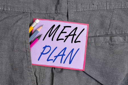 Text sign showing Meal Plan. Business photo text act of taking time to plan any number of meals for the week Writing equipment and purple note paper inside pocket of man work trousers