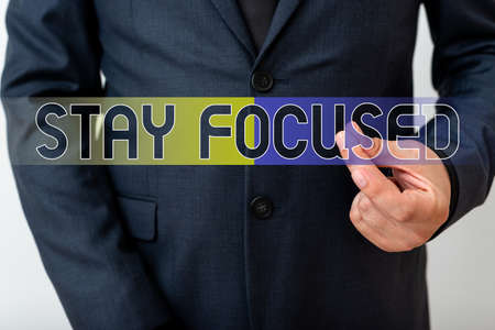 Writing note showing Stay Focused. Business concept for Be attentive Concentrate Prioritize the task Avoid distractions Model with pointing hand finger symbolizing navigation progress growth