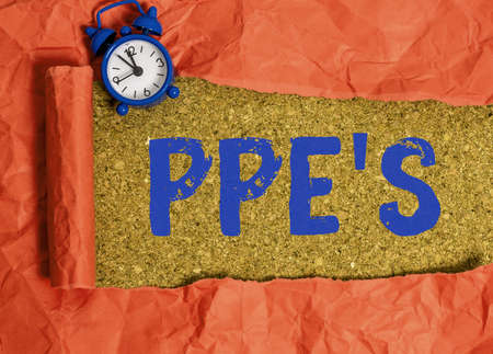 Handwriting text Ppe s is. Conceptual photo Specialized equipment for protection against health and safety hazard Rolled ripped torn cardboard placed above a wooden classic table backdrop Фото со стока