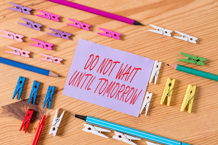 Text sign showing Do Not Wait Until Tomorrow. Business photo text needed to do it right away Urgent Better do now Colored clothespin papers empty reminder wooden floor background office Foto de archivo