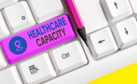 Writing note showing Healthcare Capacity. Business concept for maximum amount of patients provided with the right medical service Colored keyboard key with accessories arranged on empty copy space