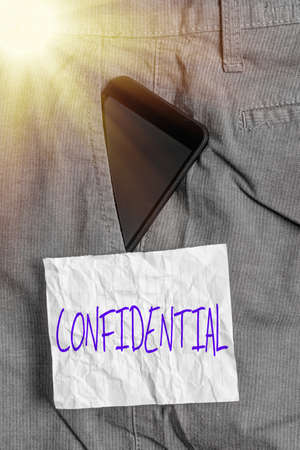 Text sign showing Confidential. Business photo text containing an individualal information whose unauthorized disclosure Smartphone device inside formal work trousers front pocket near note paper
