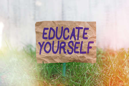Word writing text Educate Yourself. Business photo showcasing prepare oneself or someone in a particular area or subject Crumpled paper attached to a stick and placed in the green grassy land
