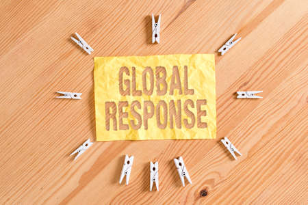 Writing note showing Global Response. Business concept for indicates the behaviour of material away from impact point Colored clothespin papers empty reminder wooden floor background office