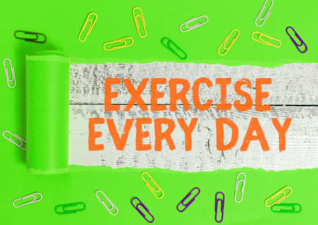 Writing note showing Exercise Every Day. Business concept for move body energetically in order to get fit and healthy Rolled ripped torn cardboard above a wooden classic table