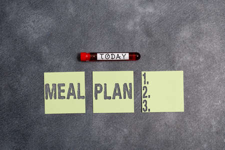 Conceptual hand writing showing Meal Plan. Concept meaning act of taking time to plan any number of meals for the week Blood sample vial medical accessories ready for examination