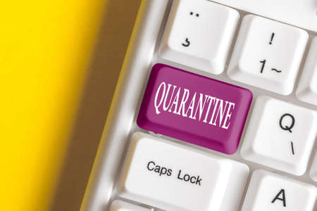 Conceptual hand writing showing Quarantine. Concept meaning restraint upon the activities of an individual or the transport of goods Colored keyboard key with accessories arranged on copy space