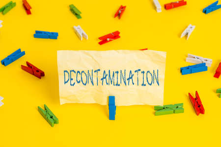 Writing note showing Decontamination. Business concept for neutralizing every presence of hazardous substances Colored clothespin papers empty reminder yellow floor background office