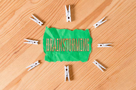 Text sign showing Brainstorming. Business photo text solving technique that involves spontaneous contribution Colored clothespin papers empty reminder wooden floor background office