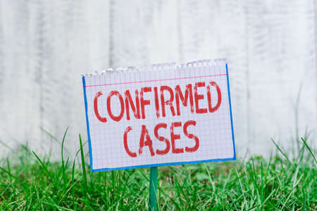 Word writing text Confirmed Cases. Business photo showcasing set of circumstances or conditions requiring action Mathematic paper attached to a stick and placed in the green grassy land
