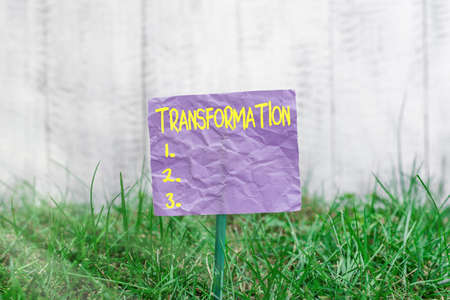 Conceptual hand writing showing Transformation. Concept meaning process, or instance of transforming or being transformed Plain paper attached to stick and placed in the grassy land