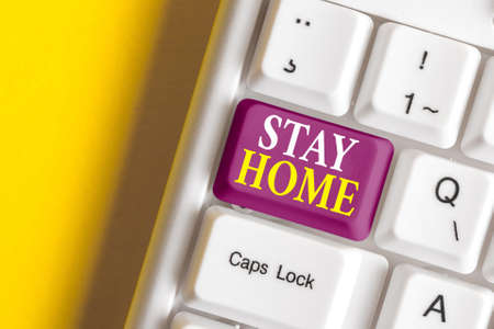 Conceptual hand writing showing Stay Home. Concept meaning not go out for an activity and stay inside the house or home Colored keyboard key with accessories arranged on copy space 版權商用圖片