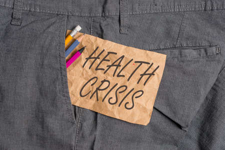 Word writing text Health Crisis. Business photo showcasing fitness problem that affects in more geographic areas Writing equipment and brown note paper inside pocket of man work trousers
