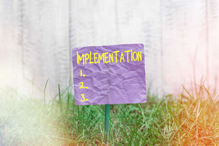 Conceptual hand writing showing Implementation. Concept meaning application of making something active or effective Plain paper attached to stick and placed in the grassy land