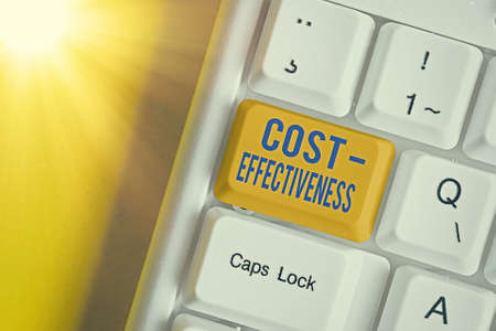 Text sign showing Cost Effectiveness. Business photo text degree to which something is effective in relation to its cost. Different colored keyboard key with accessories arranged on empty copy space 免版税图像