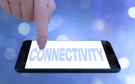 Conceptual hand writing showing Connectivity. Concept meaning quality, state, or capability of being connective or connected Modern gadgets white screen under colorful bokeh background