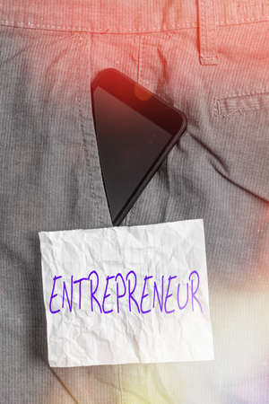 Text sign showing Entrepreneur. Business photo text one who organizes and assumes the risks of a business Smartphone device inside formal work trousers front pocket near note paper
