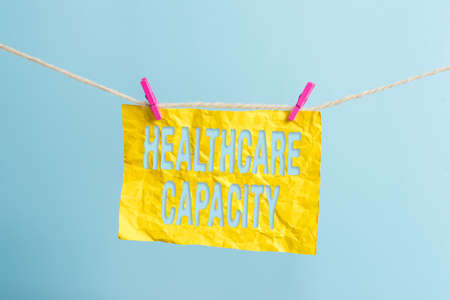 Word writing text Healthcare Capacity. Business photo showcasing maximum amount of patients provided with the right medical service Clothesline clothespin rectangle shaped paper reminder white wood desk 版權商用圖片