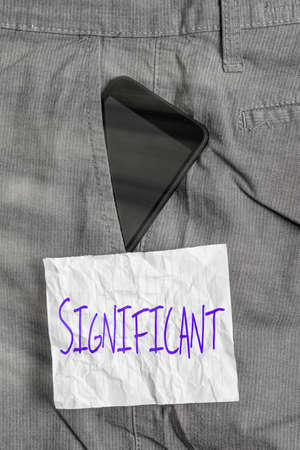 Text sign showing Significant. Business photo text sufficiently great or important to be worthy of attention Smartphone device inside formal work trousers front pocket near note paper