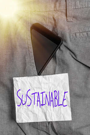 Text sign showing Sustainable. Business photo text the ability to be sustained, supported, upheld, or confirmed Smartphone device inside formal work trousers front pocket near note paper Stock Photo