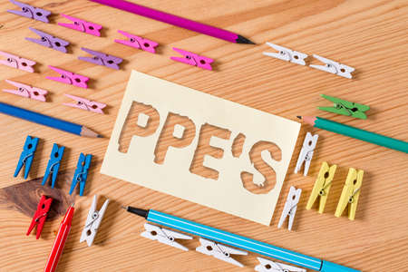 Handwriting text Ppe s is. Conceptual photo Specialized equipment for protection against health and safety hazard Colored clothespin papers empty reminder wooden floor background office Фото со стока