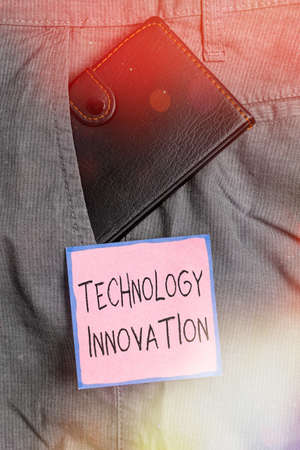 Handwriting text writing Technology Innovation. Conceptual photo significant technological changes of products Small little wallet inside man trousers front pocket near notation paper 免版税图像