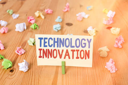 Conceptual hand writing showing Technology Innovation. Concept meaning significant technological changes of products Colored crumpled papers wooden floor background clothespin 免版税图像