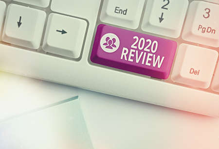 Conceptual hand writing showing 2020 Review. Concept meaning New trends and prospects in tourism or services for 2020 Colored keyboard key with accessories arranged on copy space