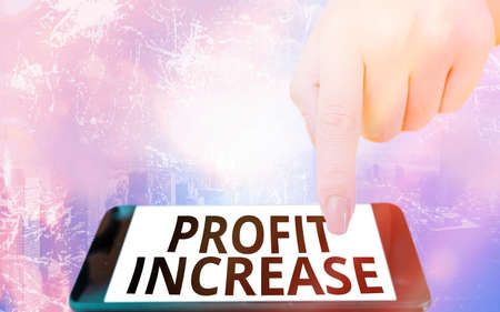 Conceptual hand writing showing Profit Increase. Concept meaning the growth in the amount of revenue gained from a business Modern gadgets white screen under colorful bokeh background 免版税图像