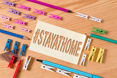 Handwriting text Hashtag Stay at home. Conceptual photo a trending label in social media related to the coronvirus outbreak Colored clothespin papers empty reminder wooden floor background office