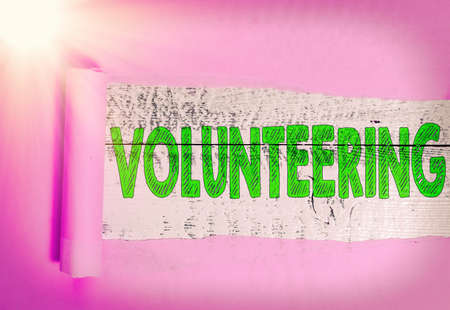 Text sign showing Volunteering. Business photo showcasing an individual who voluntarily expresses a willingness to undertake Rolled ripped torn cardboard placed above a wooden classic table backdrop