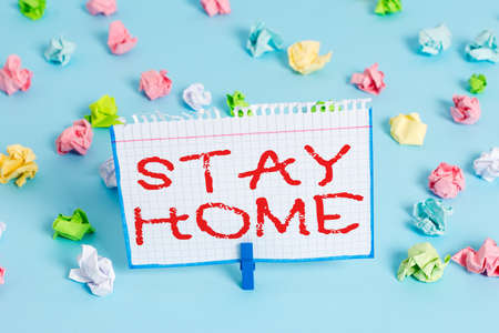 Handwriting text Stay Home. Conceptual photo not go out for an activity and stay inside the house or home Colored crumpled papers empty reminder blue floor background clothespin 版權商用圖片