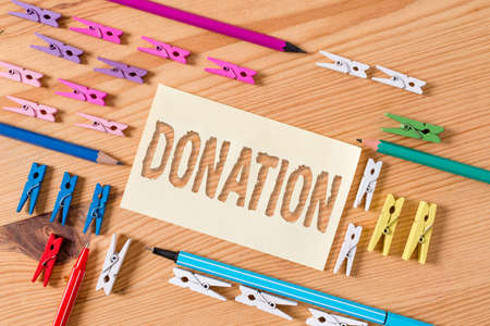 Handwriting text Donation. Conceptual photo something that is given to a charity, especially a sum of money Colored clothespin papers empty reminder wooden floor background office