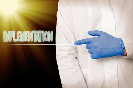 Conceptual hand writing showing Implementation. Concept meaning application of making something active or effective Displaying Sticker Paper Accessories With Medical Gloves On