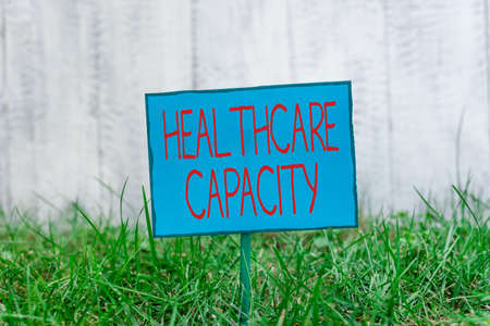 Conceptual hand writing showing Healthcare Capacity. Concept meaning maximum amount of patients provided with the right medical service Plain paper attached to stick and placed in the grassy land