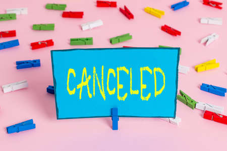 Text sign showing Canceled. Business photo showcasing to decide not to conduct or perform something planned or expected Colored clothespin papers empty reminder pink floor background office pin