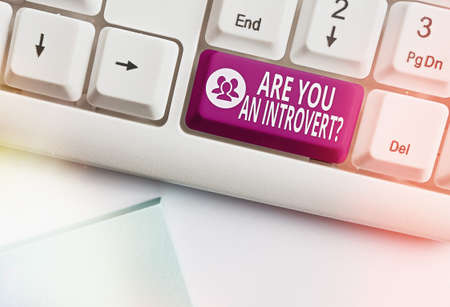 Conceptual hand writing showing Are You An Introvertquestion. Concept meaning an individual who tends to turn inward mentally Colored keyboard key with accessories arranged on copy space Stockfoto