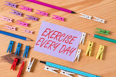 Text sign showing Exercise Every Day. Business photo text move body energetically in order to get fit and healthy Colored clothespin papers empty reminder wooden floor background office