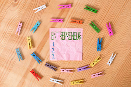 Conceptual hand writing showing Entrepreneur. Concept meaning one who organizes and assumes the risks of a business Colored crumpled papers wooden floor background clothespin