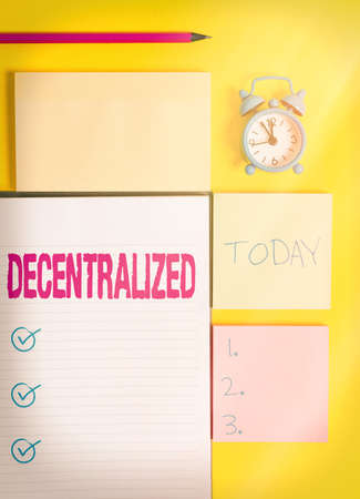 Text sign showing Decentralized. Business photo showcasing move departments away from a single administrative center Colored empty papers with copy space on the yellow background table Banco de Imagens