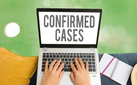 Word writing text Confirmed Cases. Business photo showcasing set of circumstances or conditions requiring action Modern gadgets with white display screen under colorful bokeh background