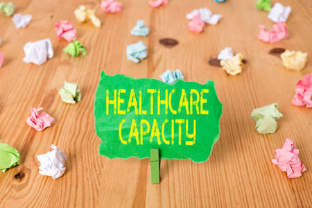 Word writing text Healthcare Capacity. Business photo showcasing maximum amount of patients provided with the right medical service Colored crumpled papers empty reminder wooden floor background clothespin