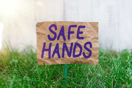 Word writing text Safe Hands. Business photo showcasing Ensuring the sterility and cleanliness of the hands for decontamination Crumpled paper attached to a stick and placed in the green grassy land
