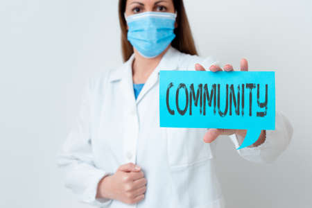 Text sign showing Community. Business photo showcasing group of showing with a common characteristics living together Laboratory technician featuring empty sticker paper accessories smartphone