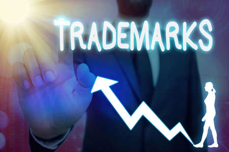 Conceptual hand writing showing Trademarks. Concept meaning legally reserved to the exclusive use of the owner as maker Arrow symbol going upward showing significant achievement